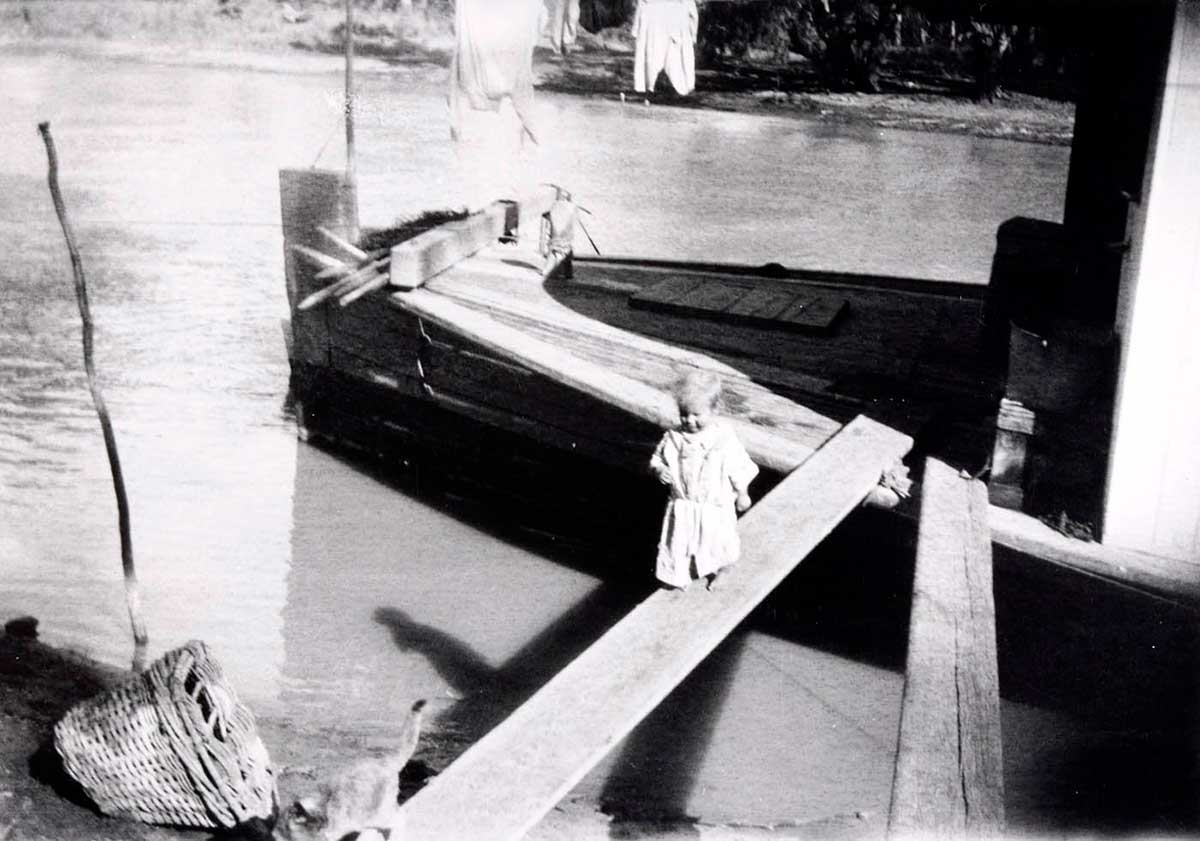 Black and white photo of a young child walking along a gangplank, following a cat.