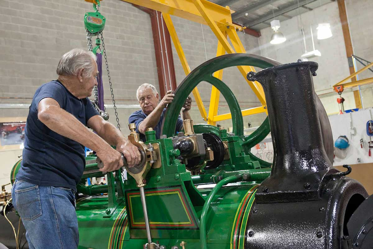 A colour photograph of two men working on a steam engine. - click to view larger image