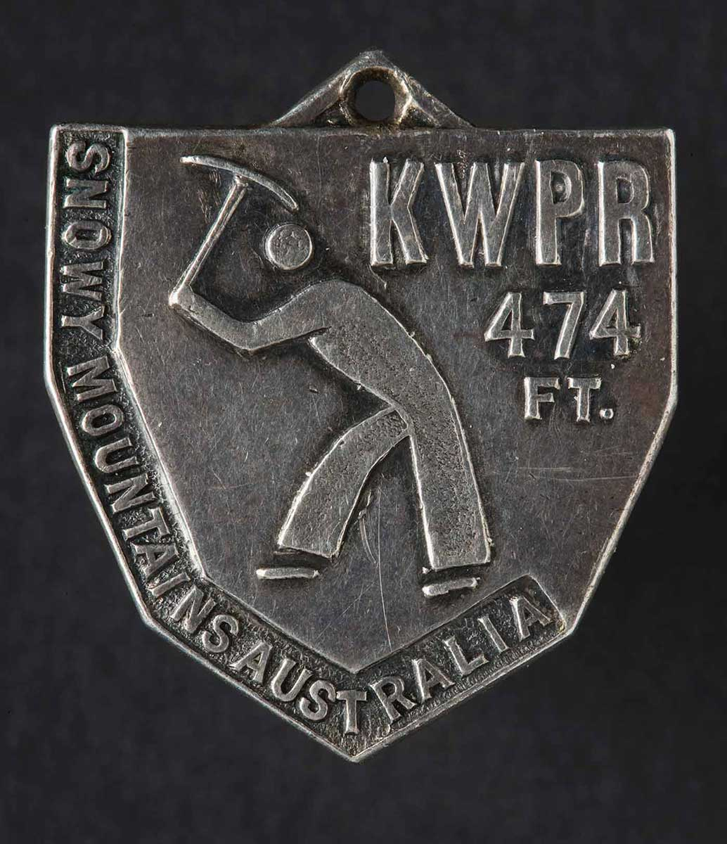 An image of a worker holding a tool above his head and in a digging stance is in the centre of the medal. 'KWPR 474 FT' is written in the top right corner and 'Snowy Mountains Australia' is written down the left hand side. - click to view larger image