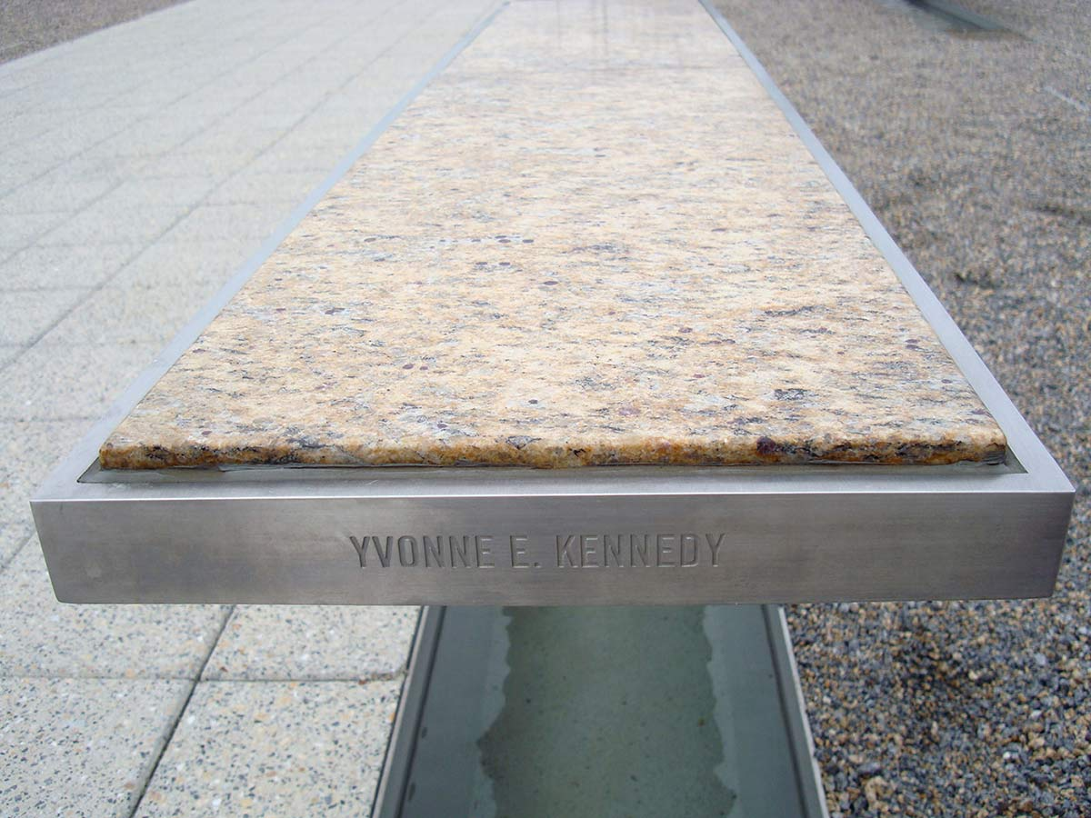 Far end of a silver rectangular metallic bench with a light marble top. 'YVONNE E. KENNEDY' is engraved in the side of the bench, which sits above a pool of water. - click to view larger image