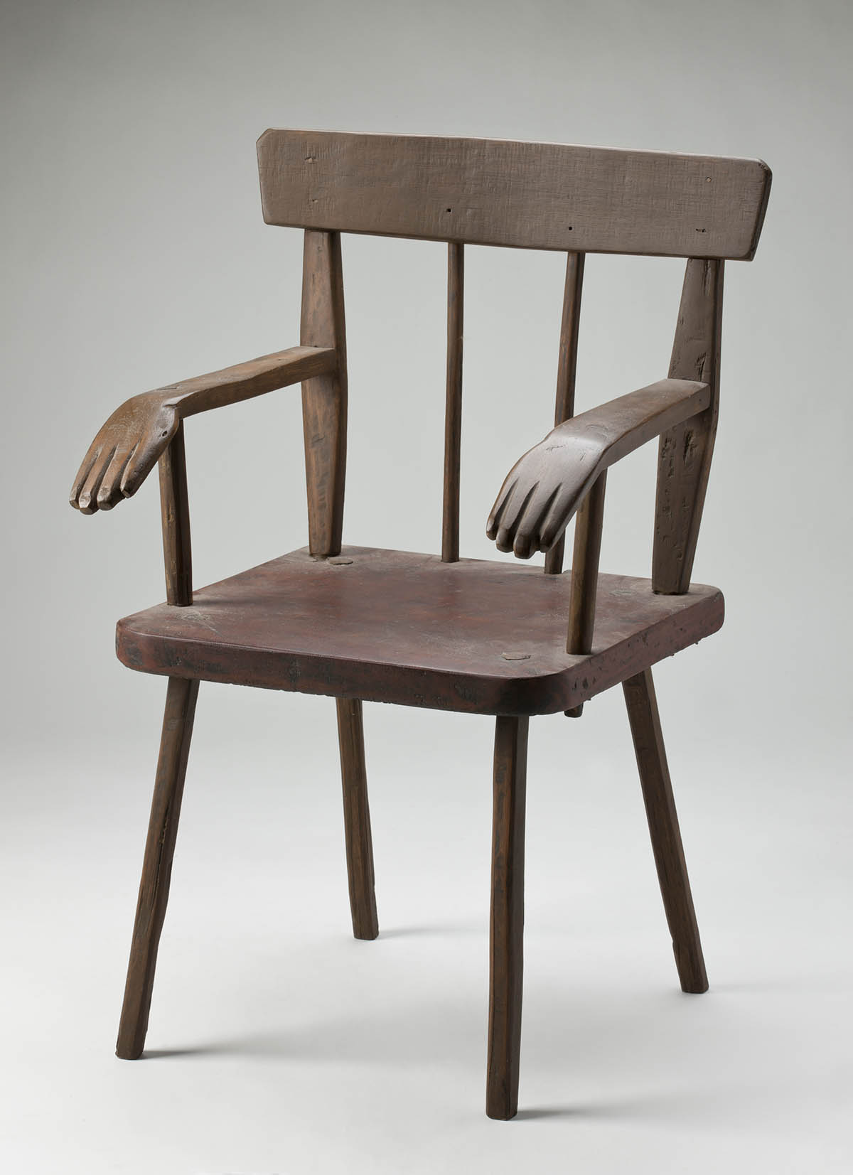 A wooden chair with decorative carved hands at the end of each arm. - click to view larger image