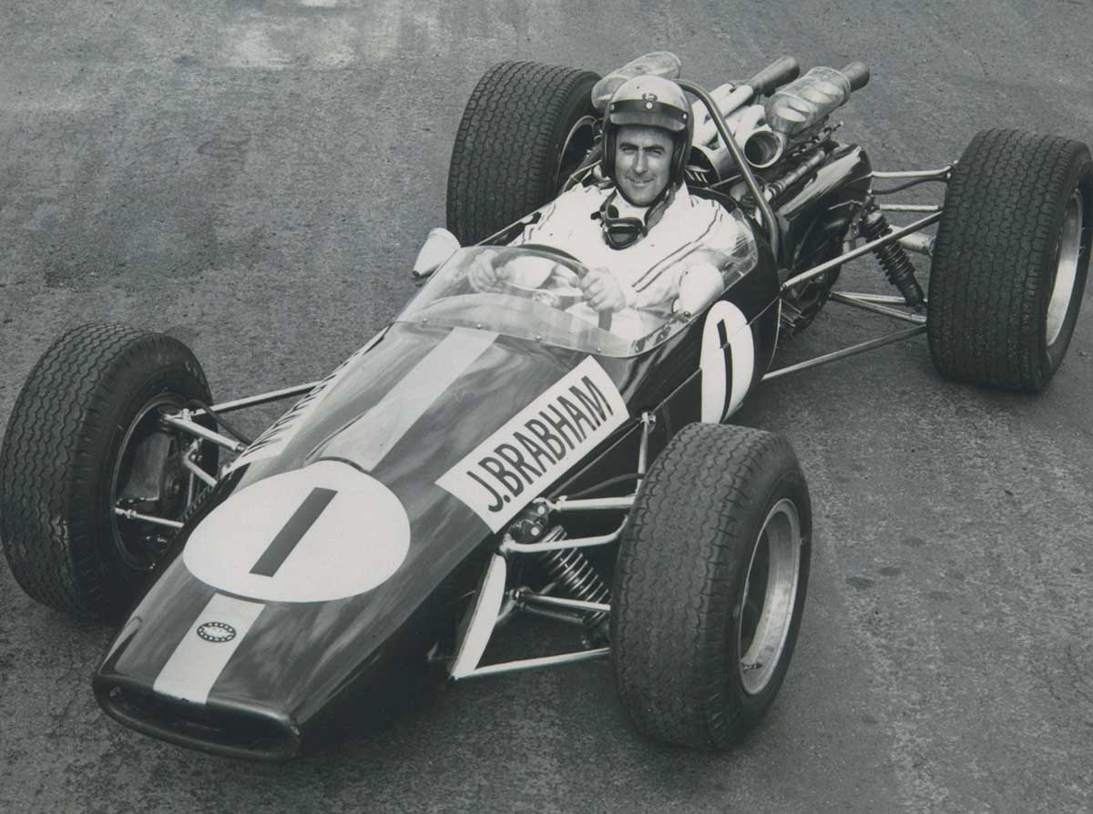 A black and white photo of a man sitting in a racing car. - click to view larger image