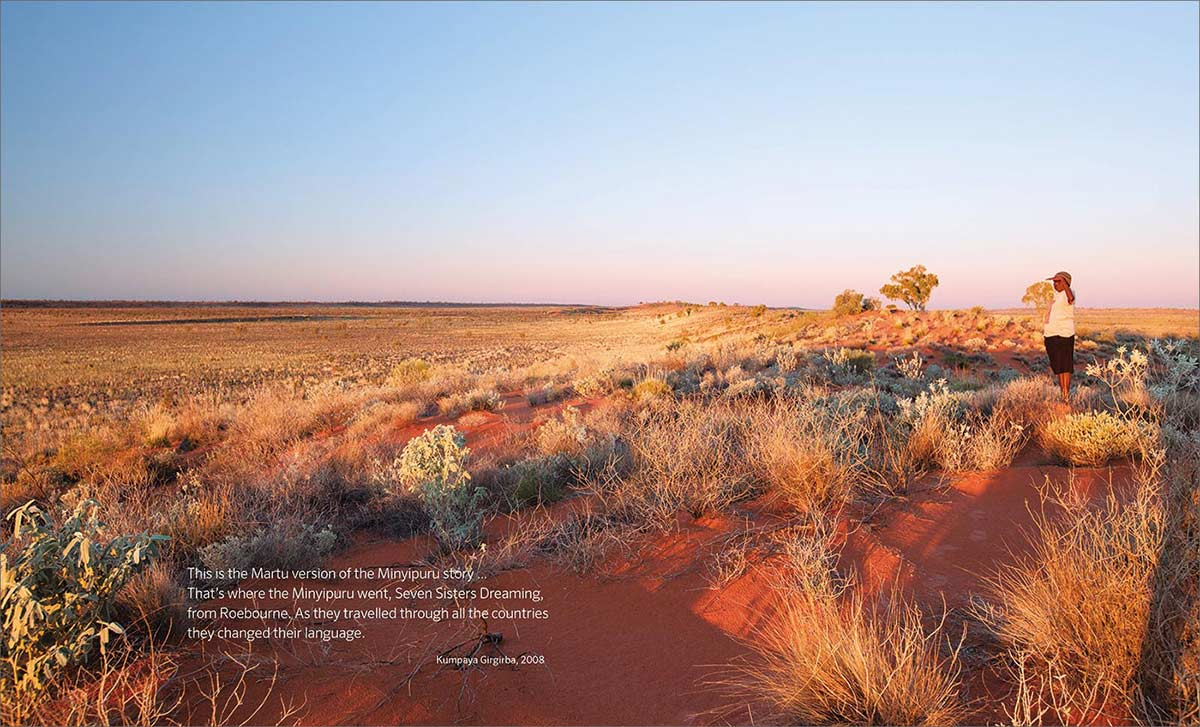 Songlines catalogue spread with a quote from Kumpaya Girgirba and a large desert landscape image - click to view larger image