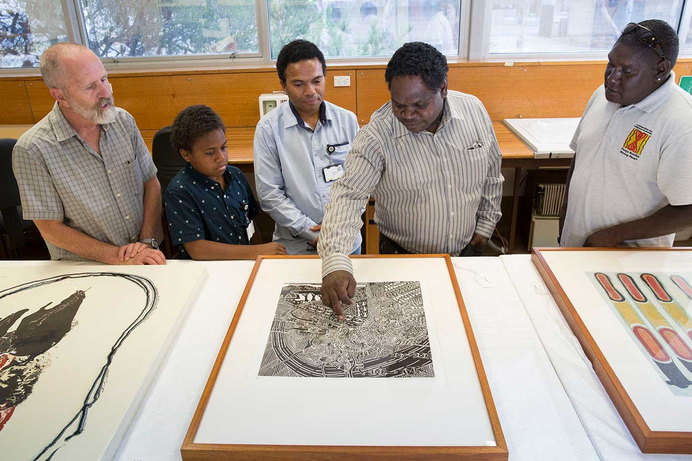 Four men and a child looking at a print on a table