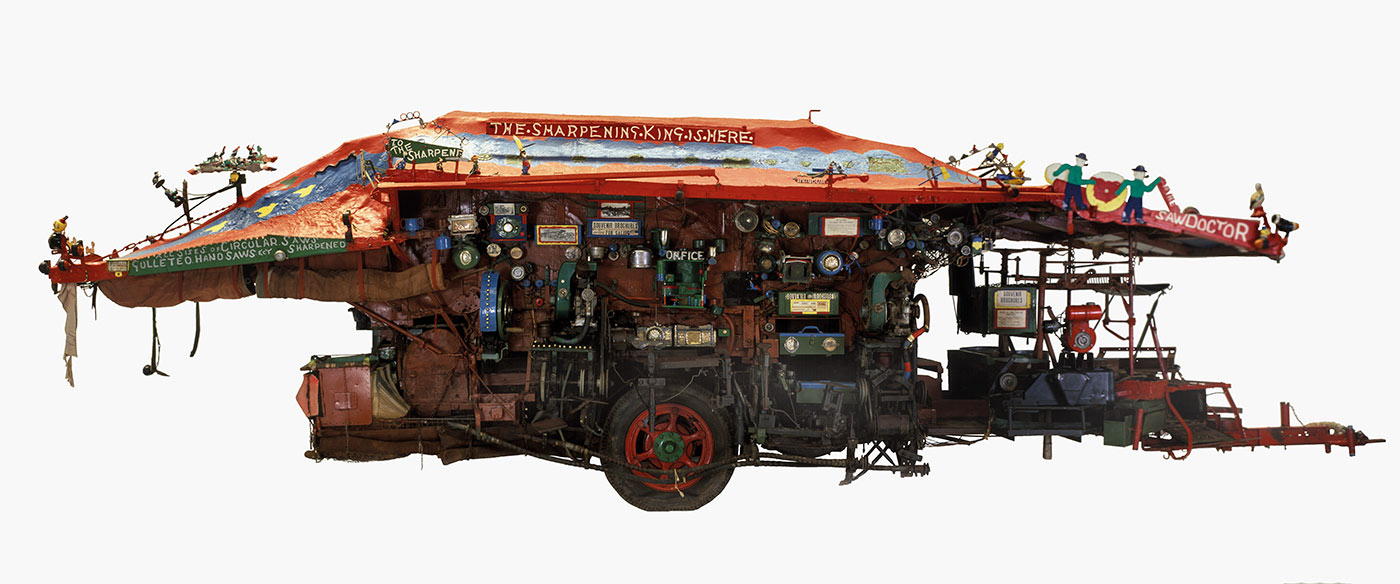 Side view of an elaborately decorated wagon on a single axle, with a red canvas roof and various tools, compartments and handmade signs.