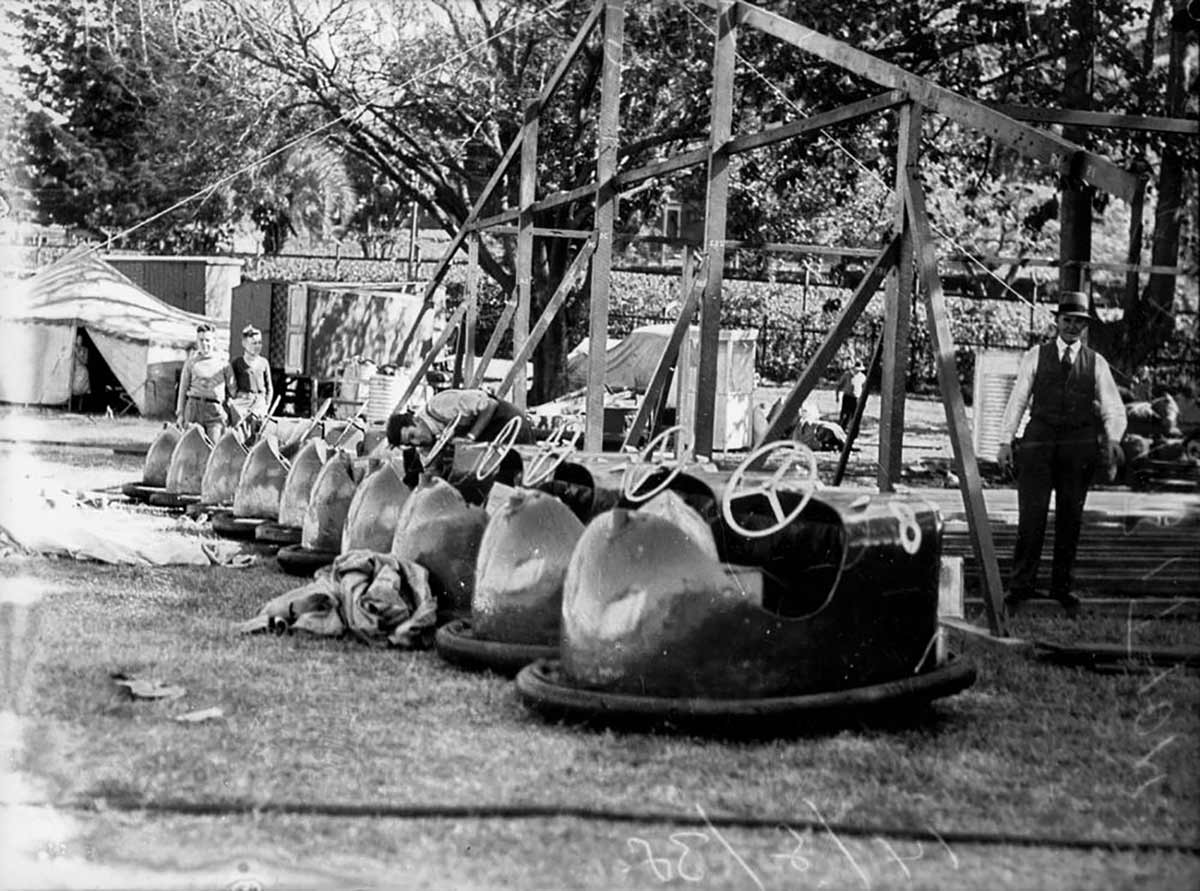 A row of dodgem cars.  Two men and two children are visible in the photo. - click to view larger image