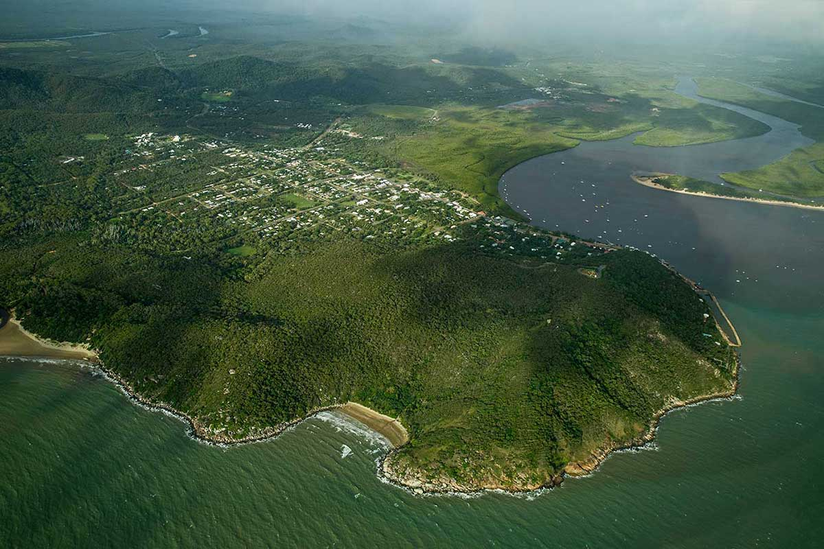 Aerial phorograph showing a town laid out alongside a river and extending to a headland. - click to view larger image