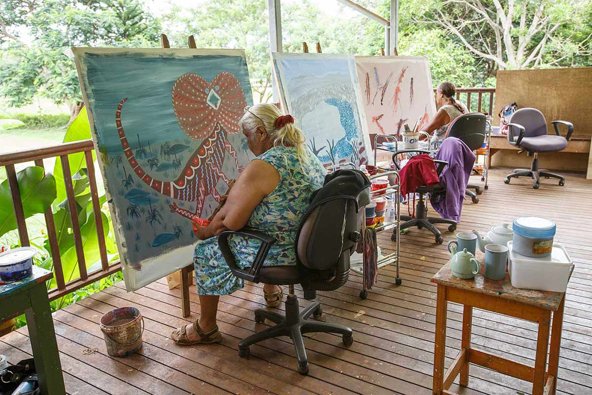 Two women working on Aboriginal paintings. - click to view larger image