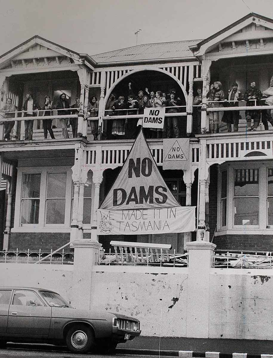 People standing on a balcony. There is a large banner with the text
