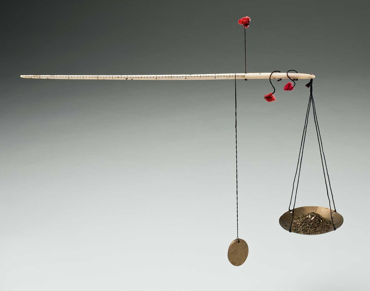 Colour photograph of a set of small scales with a long white rod at top and a small disc hanging at one end, alongside a suspended concave tray. Small pieces of a gold-coloured substance are piled on the tray.  - click to view larger image