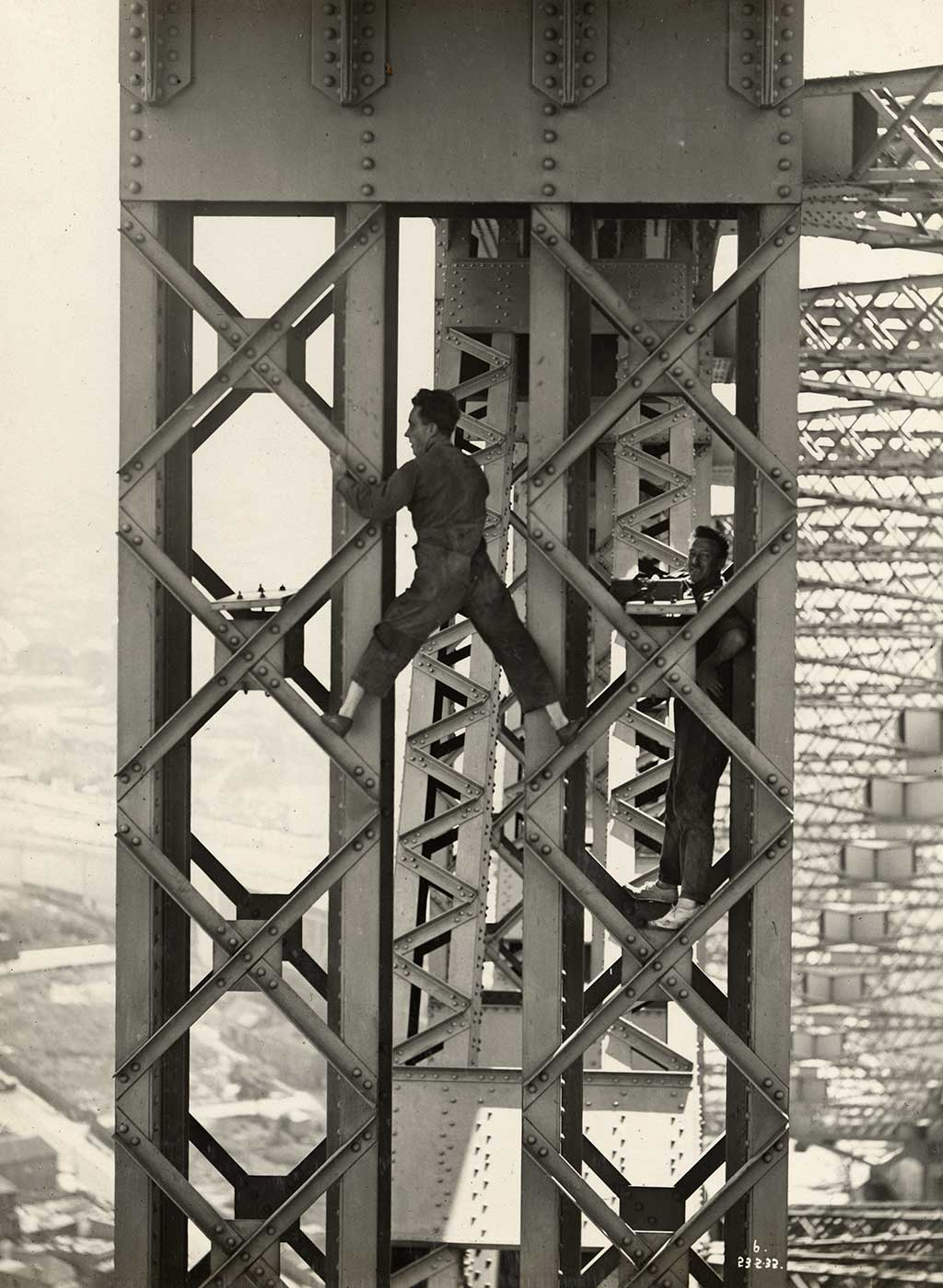 A man stands astride two sections of metal bridgework. He wars overalls and shoes without socks. Another man stands smiling while resting on another section of bridge at right. - click to view larger image