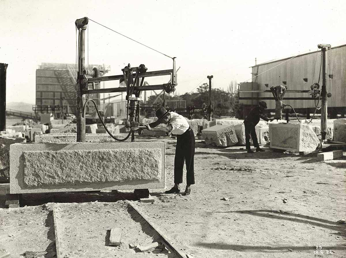 Black and white photograph of two men working on large granite blocks.  - click to view larger image