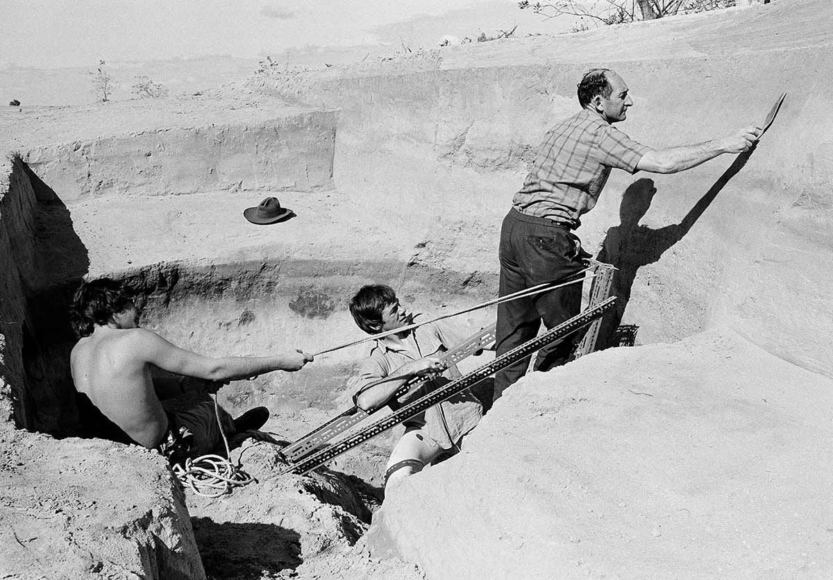 Black and white photograph of three men working in a pit in a desert scene. Two men pull on ropes supporting a metal structure where a third man stands with a trowel in his extended right arm. - click to view larger image