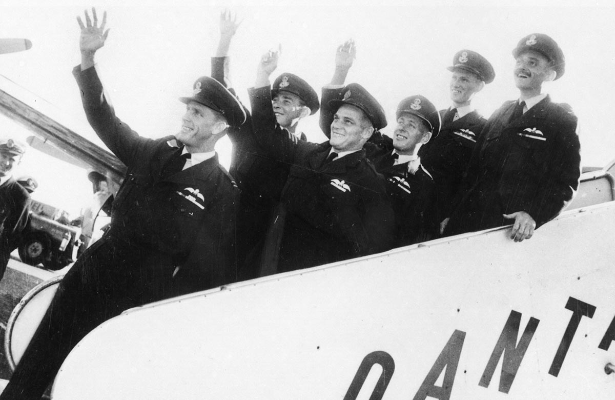 Six men in RAAF uniform smiling and waving while standing on the moveable staircase attached to a plane.