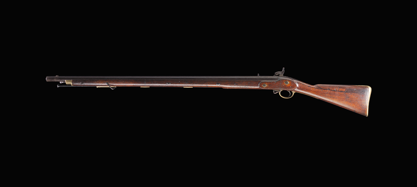A long-barelled gun with a wooden stock and brass furnishings - click to view larger image