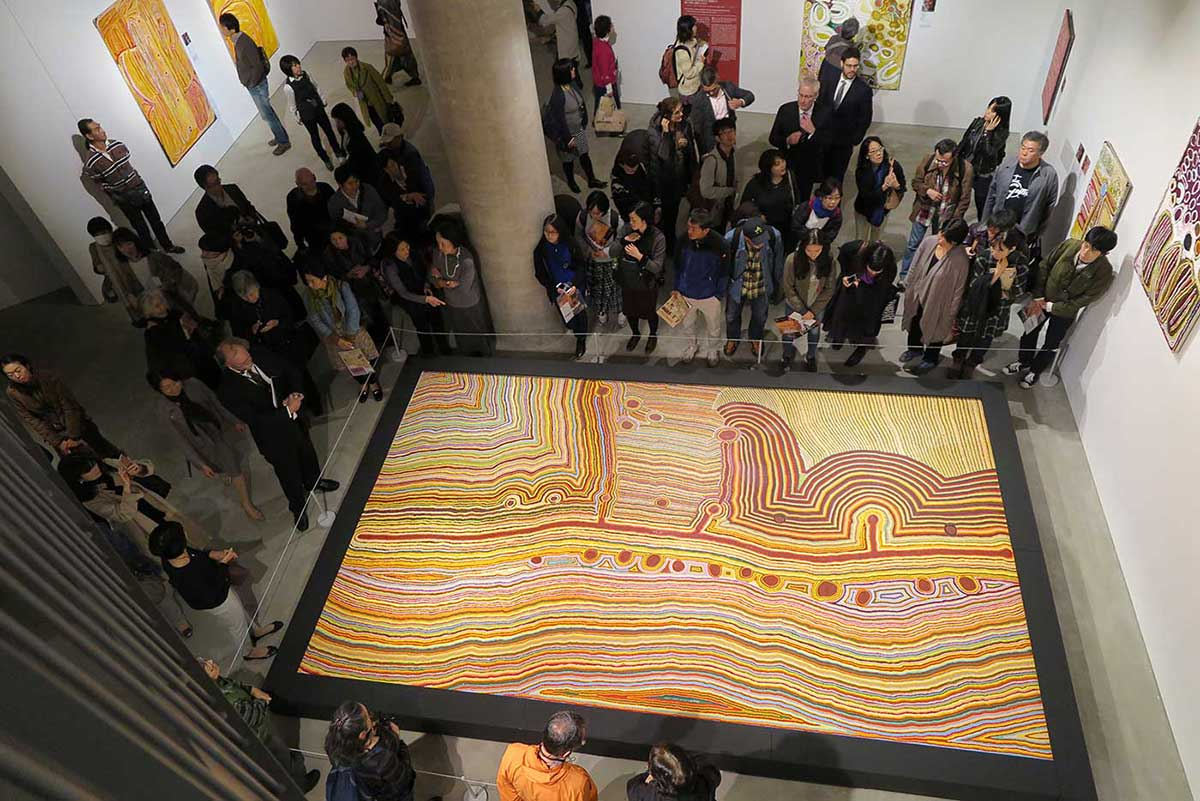 Visitors looking at a large Indigenous artwork in a Museum gallery. - click to view larger image