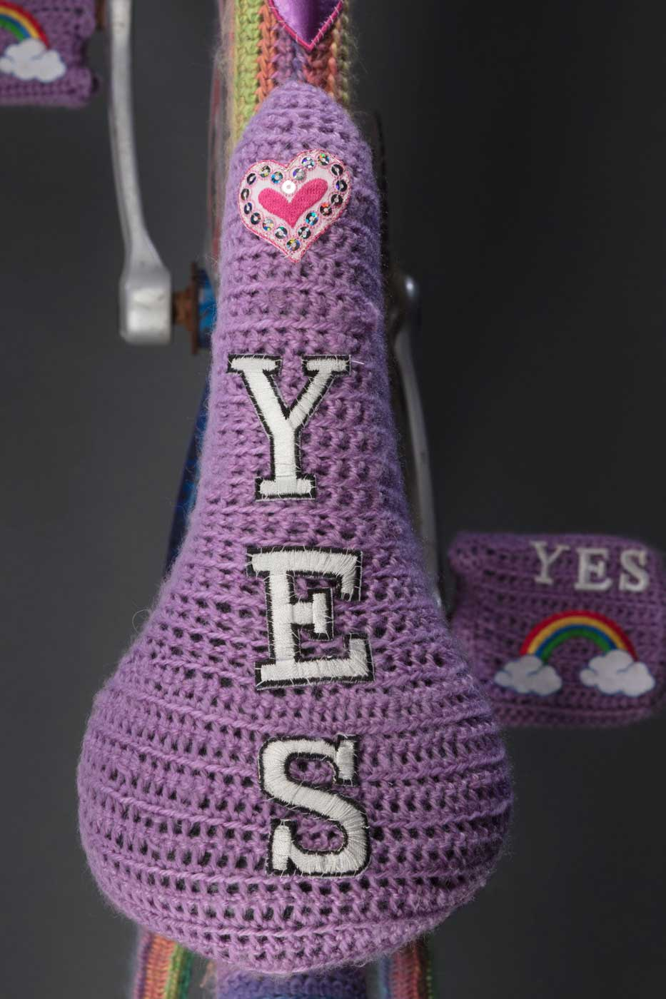 Bike seat covered in mauve wool with the word 'YES' woven vertically beneath a red heart - click to view larger image