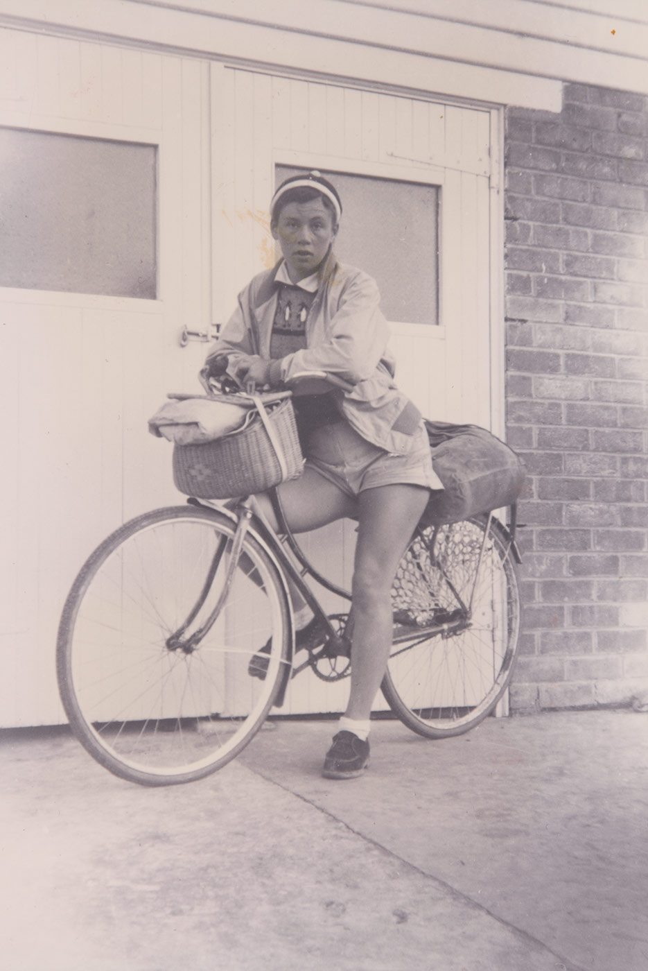 Black and white photograph of Reima Miezitis sitting her bike. - click to view larger image