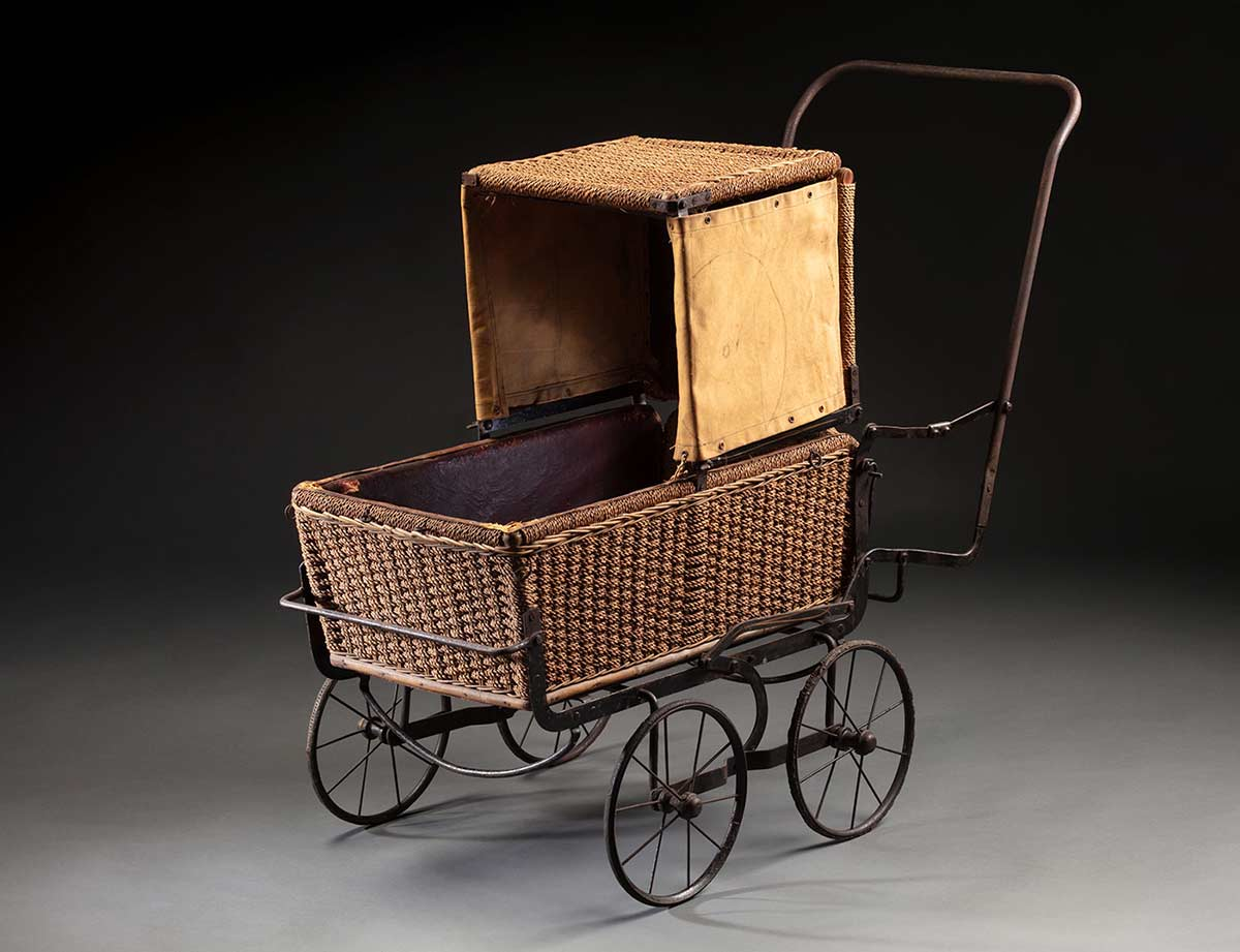 A folding pram (perambulator) with a metal frame and woven wicker body and hood that has separate canvas flaps attached to the left and right side, 1930s.