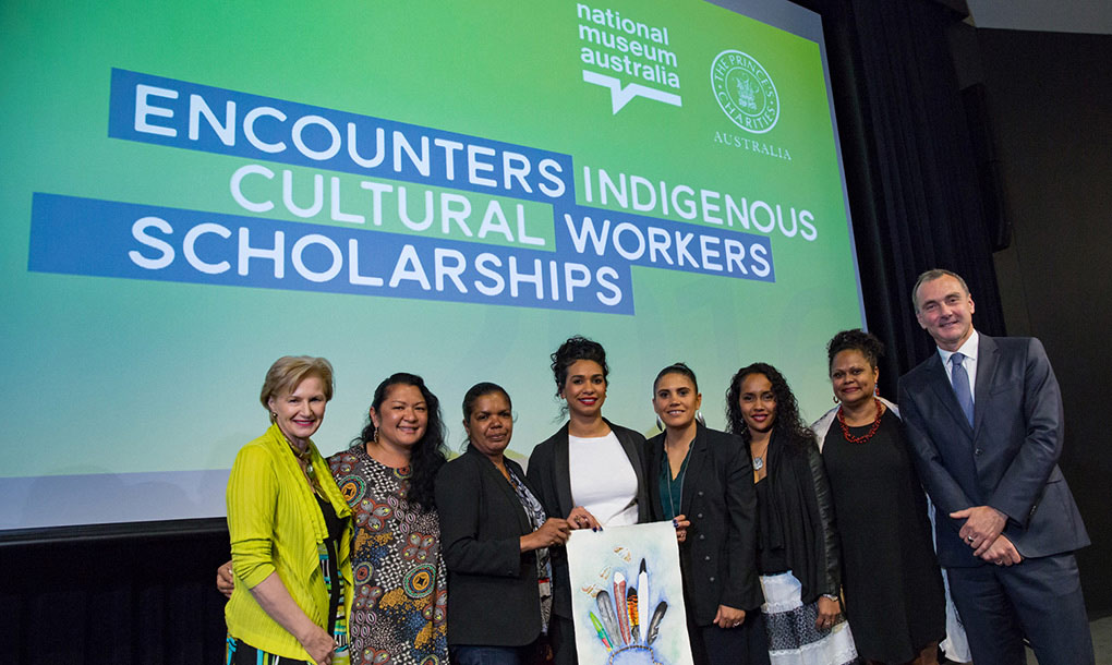 A group of women and one man pose for the camera in front of a large screen which projects the words 'ENCOUNTERS INDIGENOUS CULTURAL WORKERS SCHOLARSHIPS'. There are two logos in the far top right-hand corner, National Museum of Australia and The Prince's Charities Australia. - click to view larger image