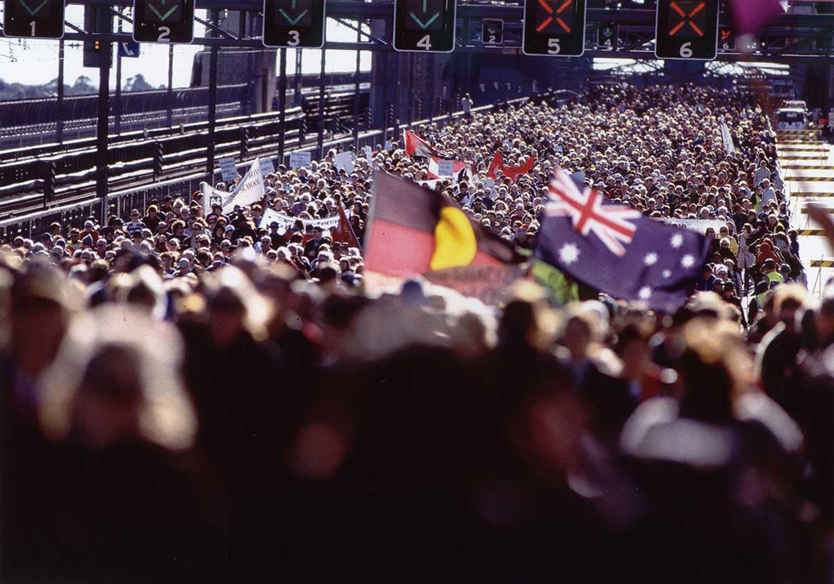 A huge crowd of people on the Sydney Harbour Bridge, with the Aboriginal flag being carried alongside the Australian flag. - click to view larger image