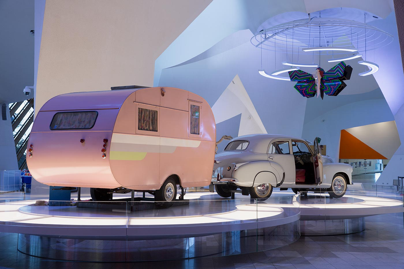 An FJ Holden and pink Propert caravan on display inside the National Museum of Australia.