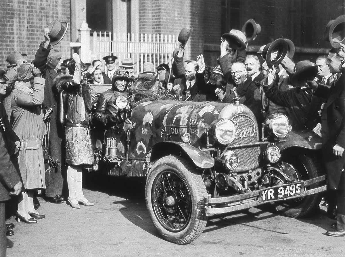 A black and white photo showing a driver seated in a car from the 1920s at the centre of a large crowds of people raising their hats.
