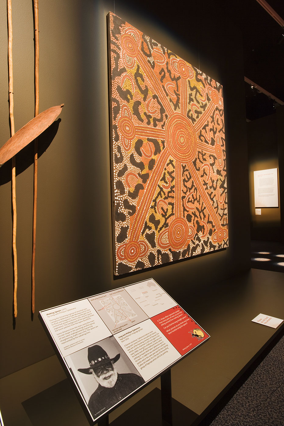 'Making Spears' dot painting, two spears and spear thrower, mounted on wall behind a text panel showing small image of artist Long Jack Phillipus Tjakamarra. - click to view larger image