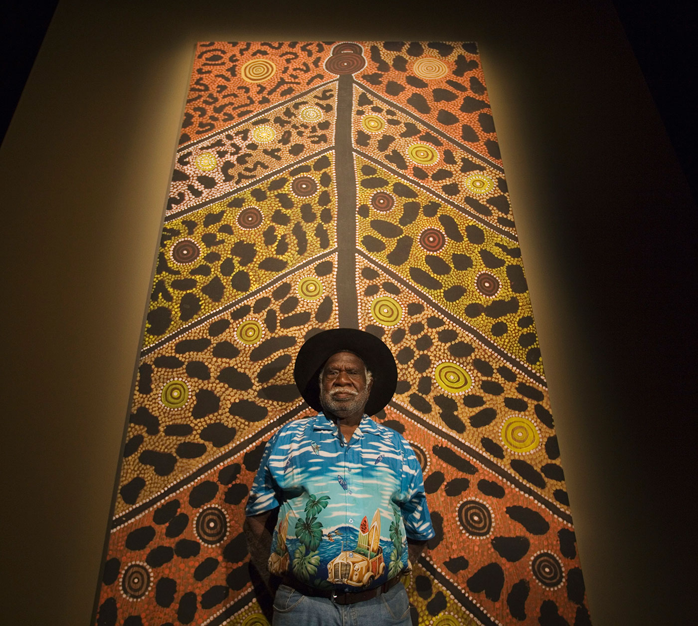 Long Jack Phillipus Tjakamarra standing in front of large painting. - click to view larger image