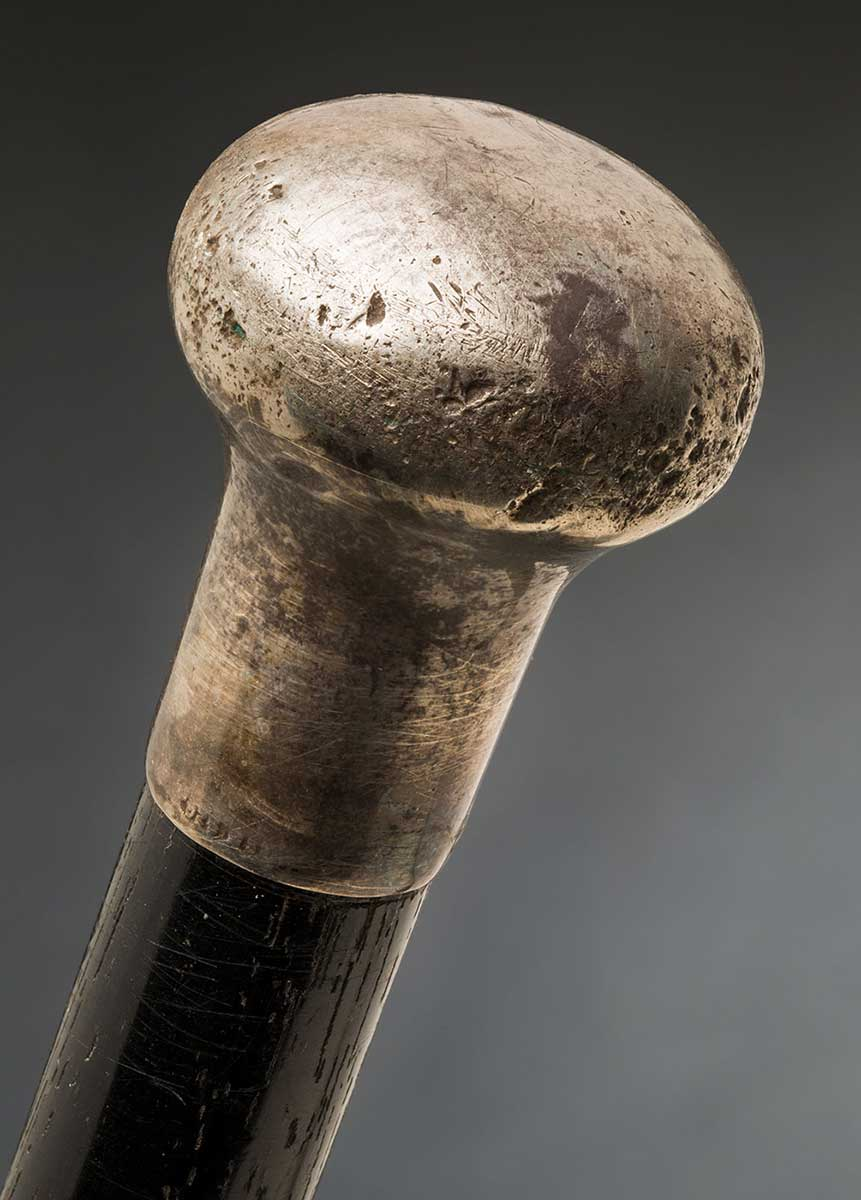 A dark wooden cane with a round silver knob. The tip of the cane is in a separate light-coloured piece of wood. There is a stamp on the silver knob which reads: '925 S'. - click to view larger image