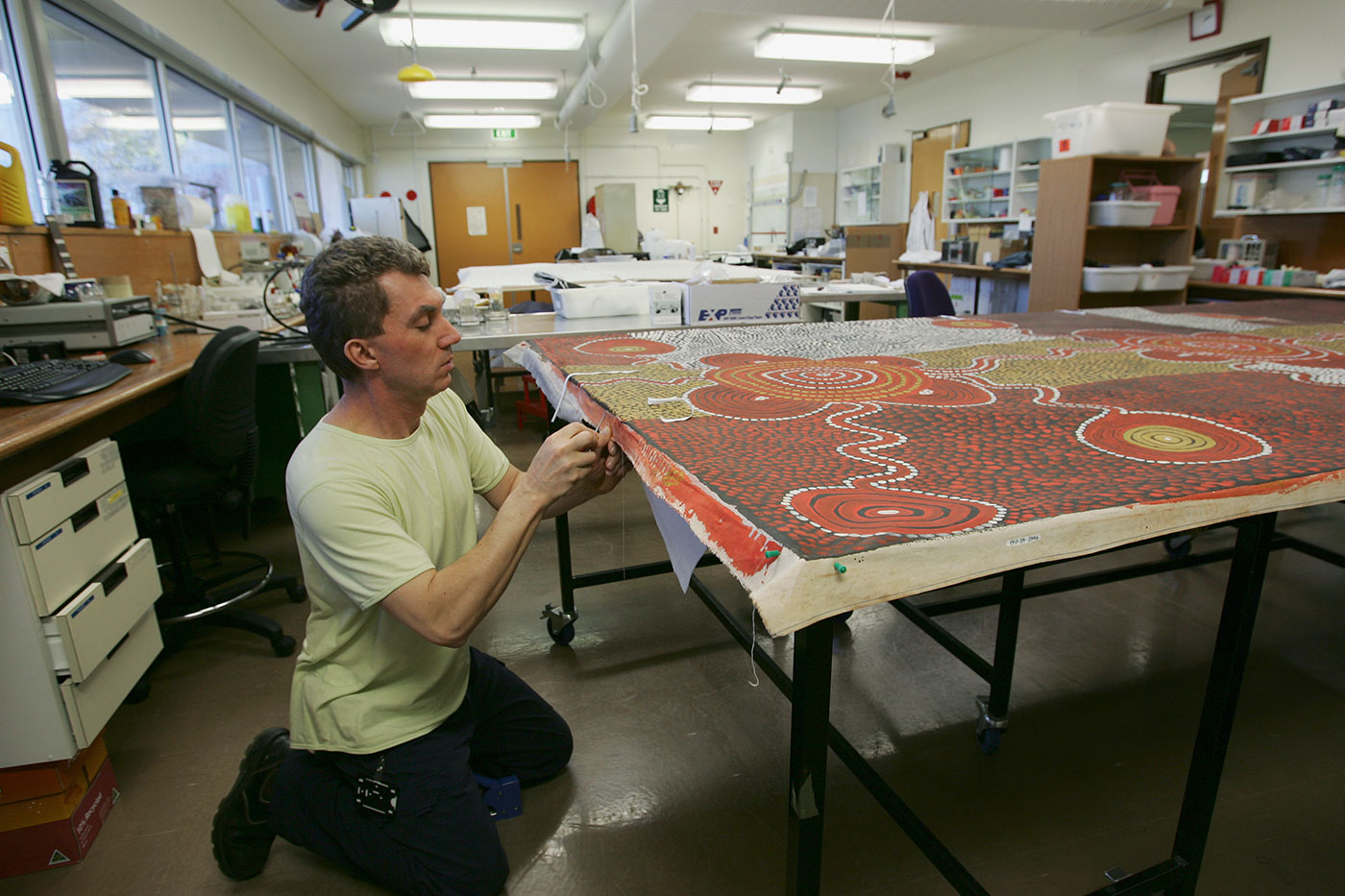 A conservator kneels to inspect edge of large canvas, with laboratory in background. - click to view larger image