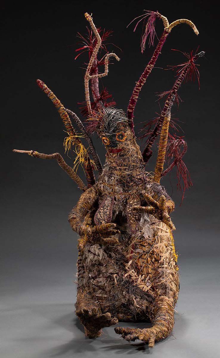 A tree sculpture baring human like features such as a face, hair, breasts, arms, fingers, legs and toes featured in a seated position. The sculpture is made of various plant and synthetic materials. - click to view larger image