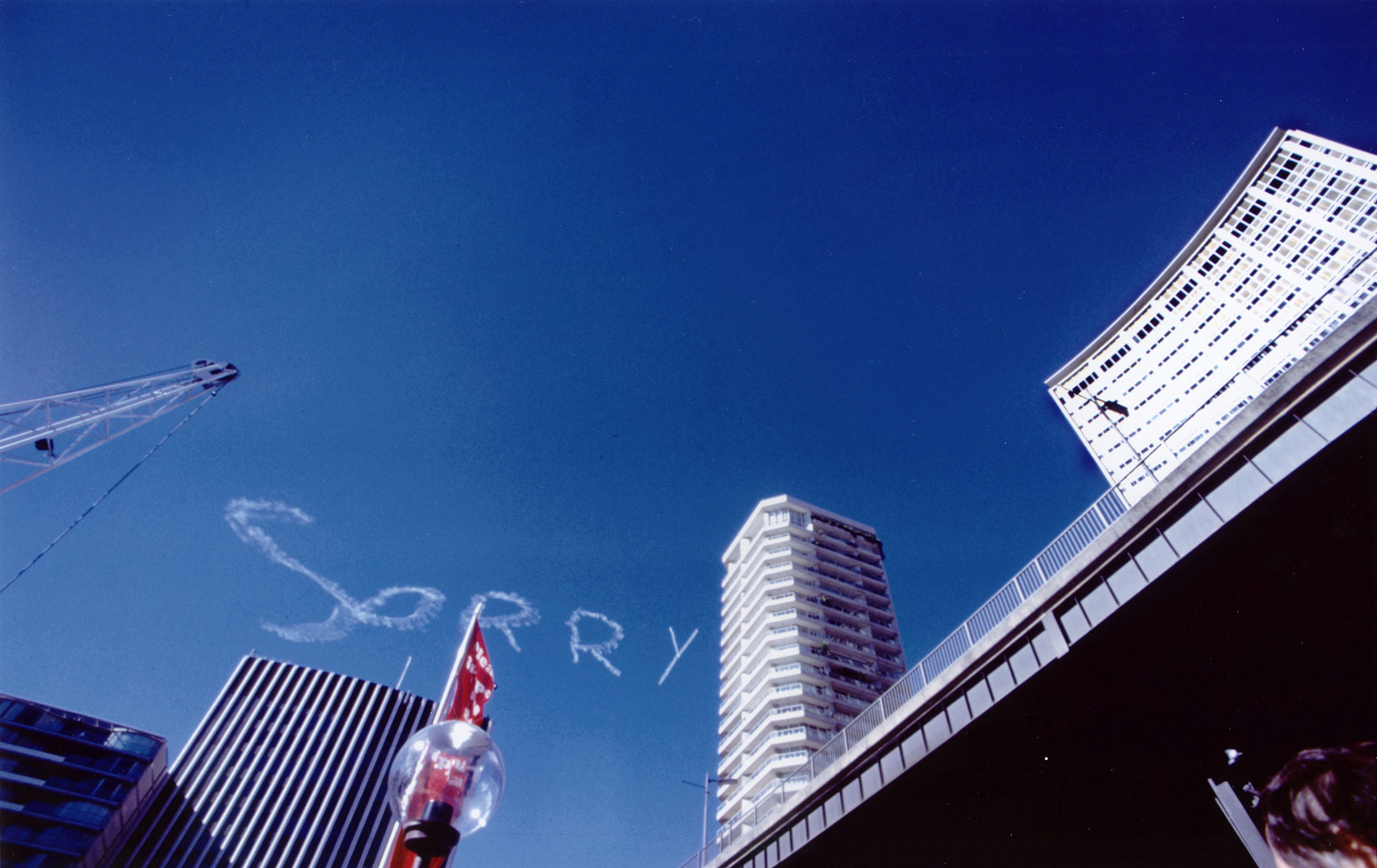 A colour photo showing 'SORRY' written in white vapour trail against a blue sky. The foregrounds shows an urban skyline with the top of a crane visible at the left and multi-storey buildings rising to the right.
