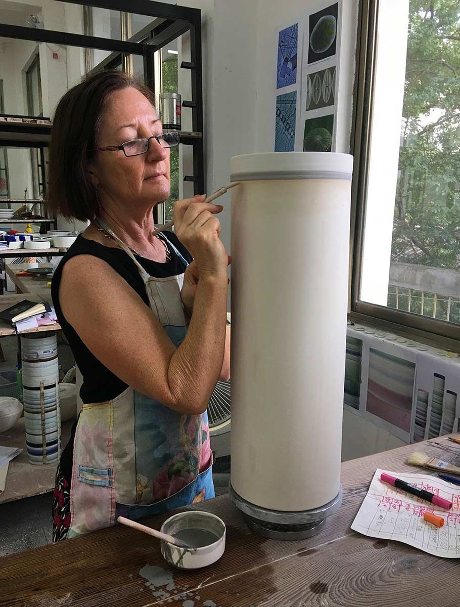 Woman painting a cylindrical object in a studio.