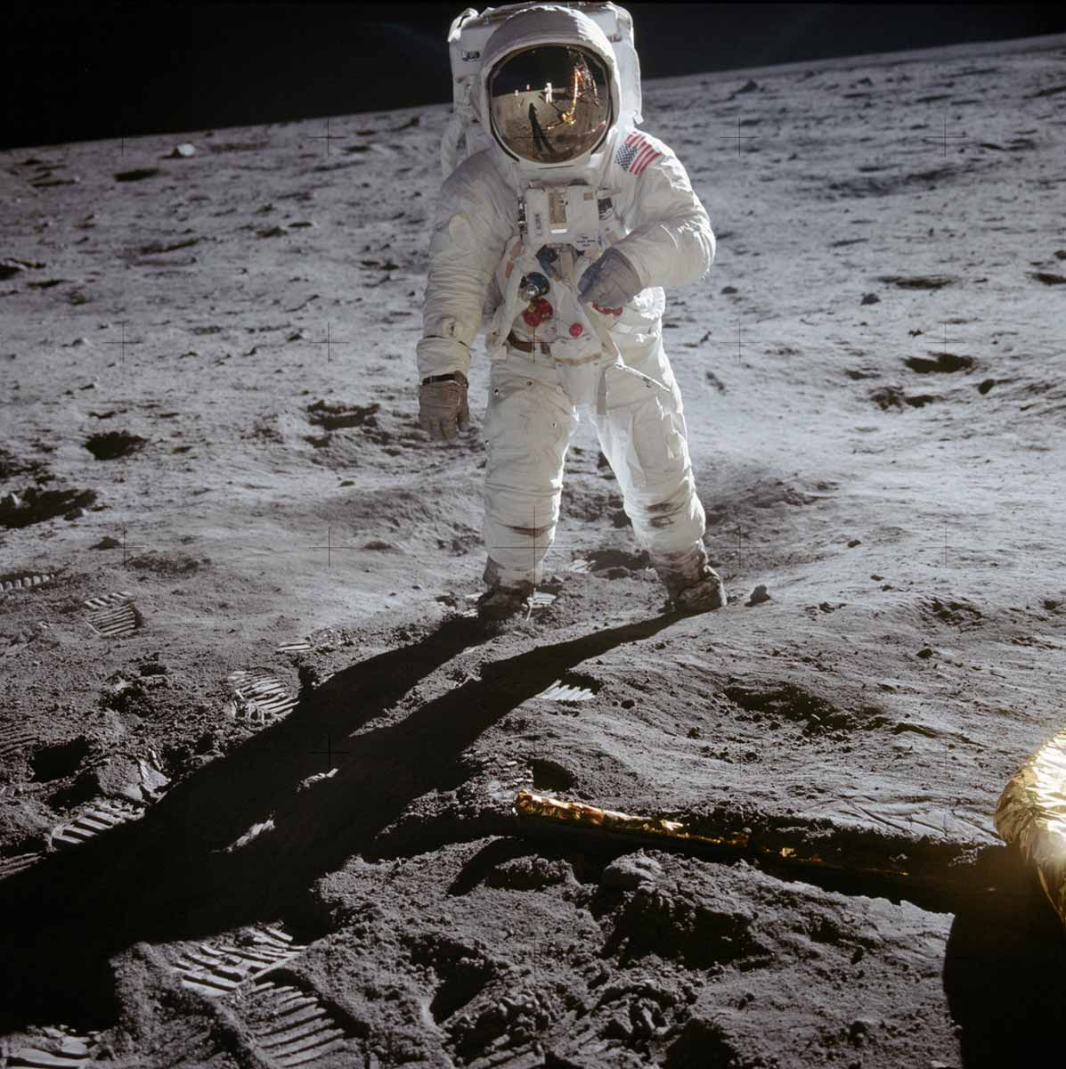 A photograph of a person, dressed in full astronaut gear, is standing on the Moon's landscape and is facing the camera. - click to view larger image