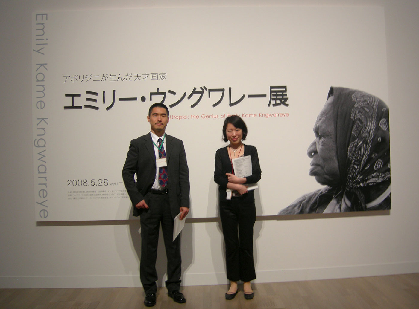 A man and woman standing in front of a large exhibition banner. - click to view larger image