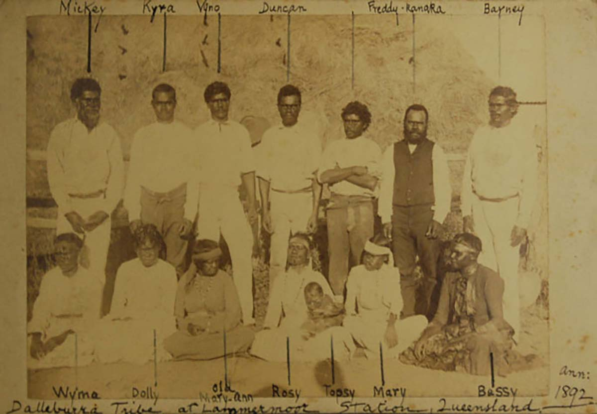 An old sepia photo of a group of men, women and children.
