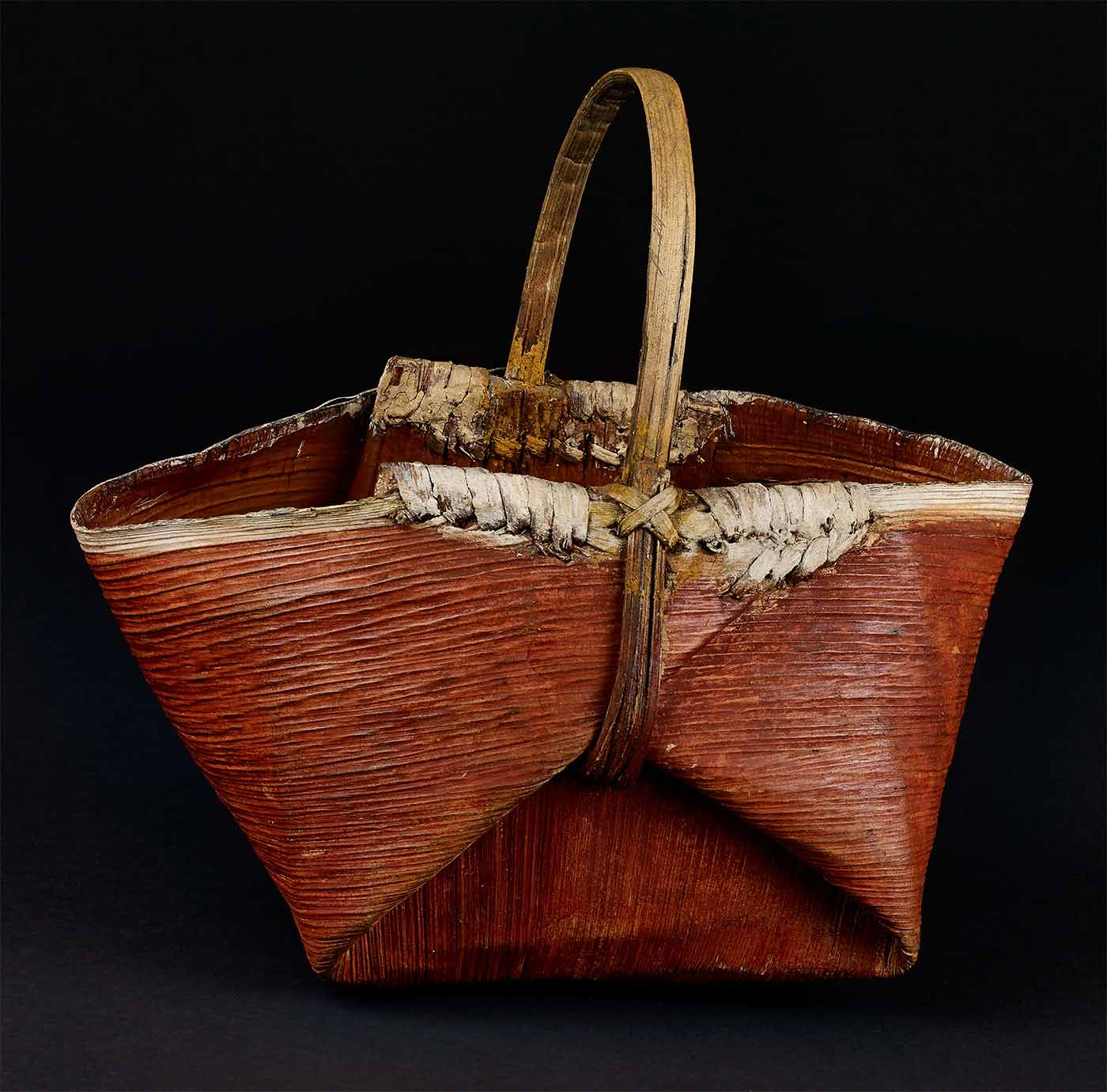 Basket made of vegetable fibre. Closely twined with complex painted decoration in white, red and dark green ochre, covering two thirds of basket leaving one section plain.