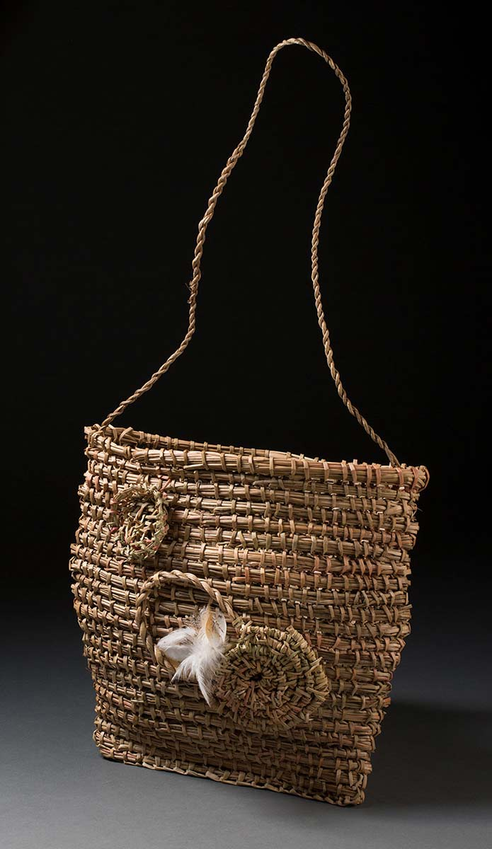 A woven bag that is almost square in shape and has a long plaited handle. The front side of the bag has woven decorative coiled circles with white and brown feathers attached. - click to view larger image