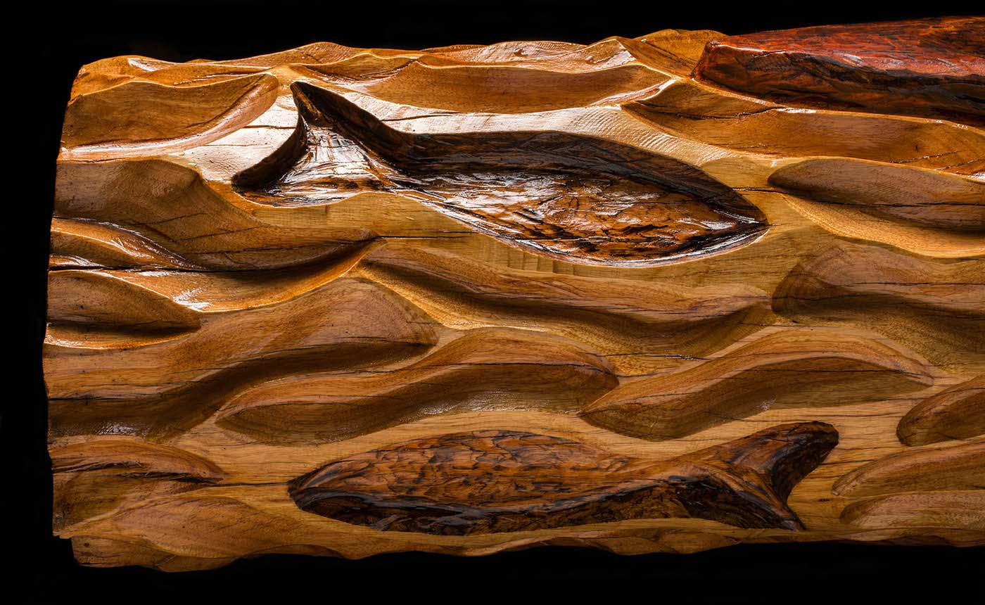 One end of a lacquered wooden pole with carved fish and wave-lines. - click to view larger image