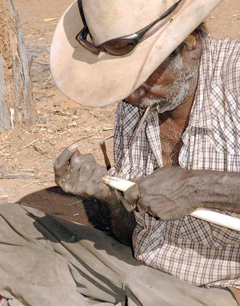 Close up of a man attaching a spear to the shaft. - click to view larger image