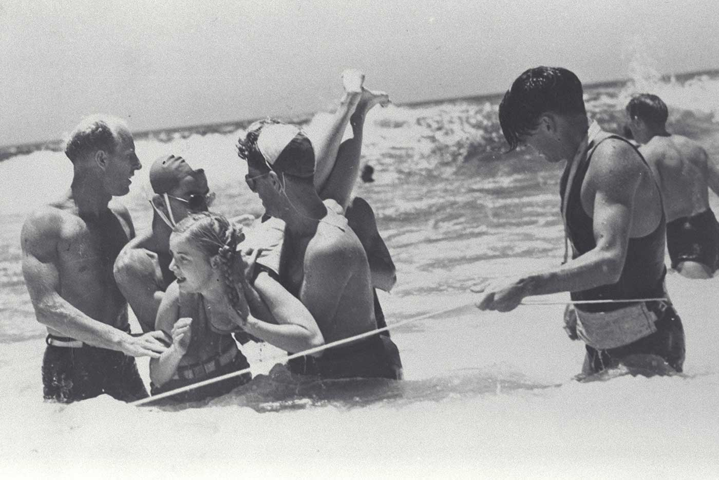 Lifesavers rescuing a young girl struggling in the surf at Kirra, Queensland in 1948.