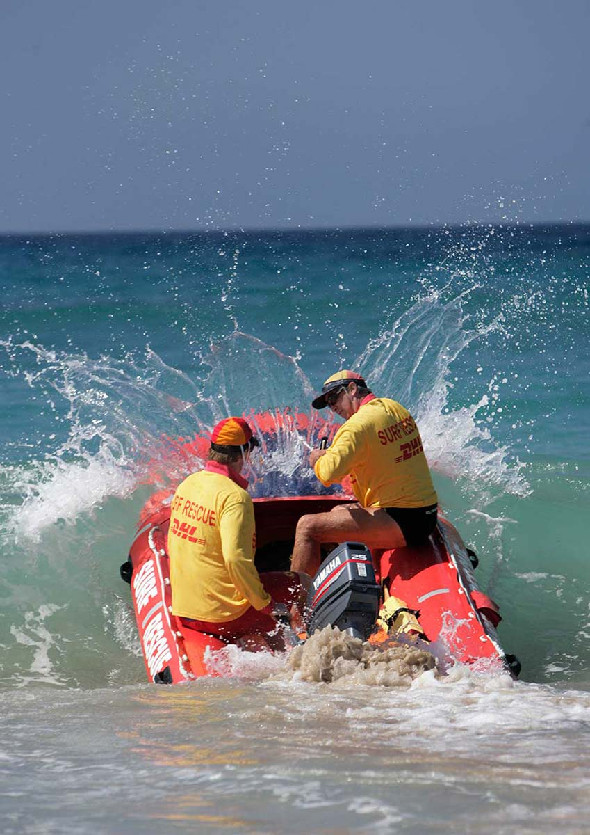 Two lifesavers in the surf in an inflatable rescue boat. - click to view larger image