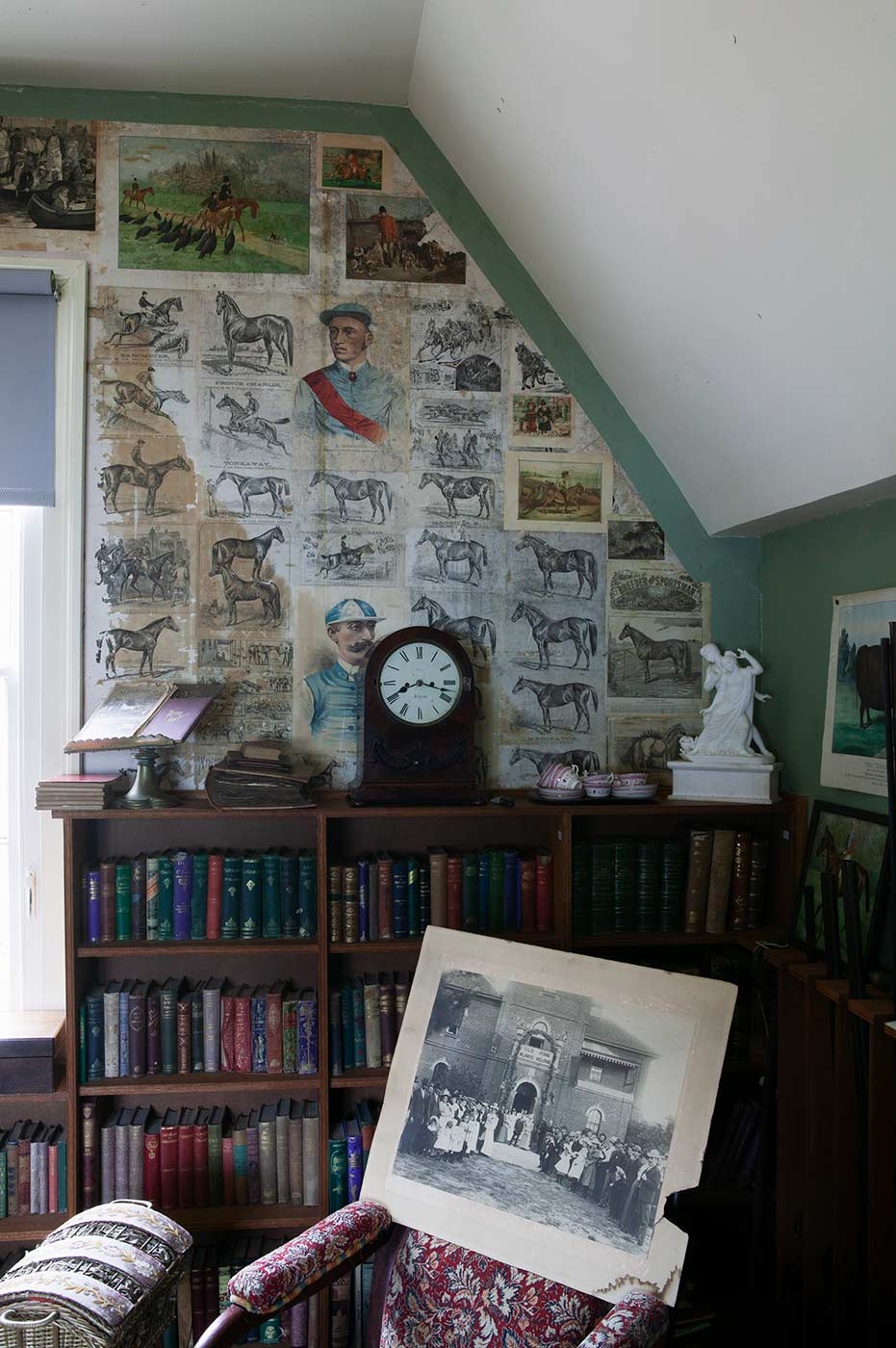 Interior view of a room filled with books, art, furniture and other various household objects. - click to view larger image