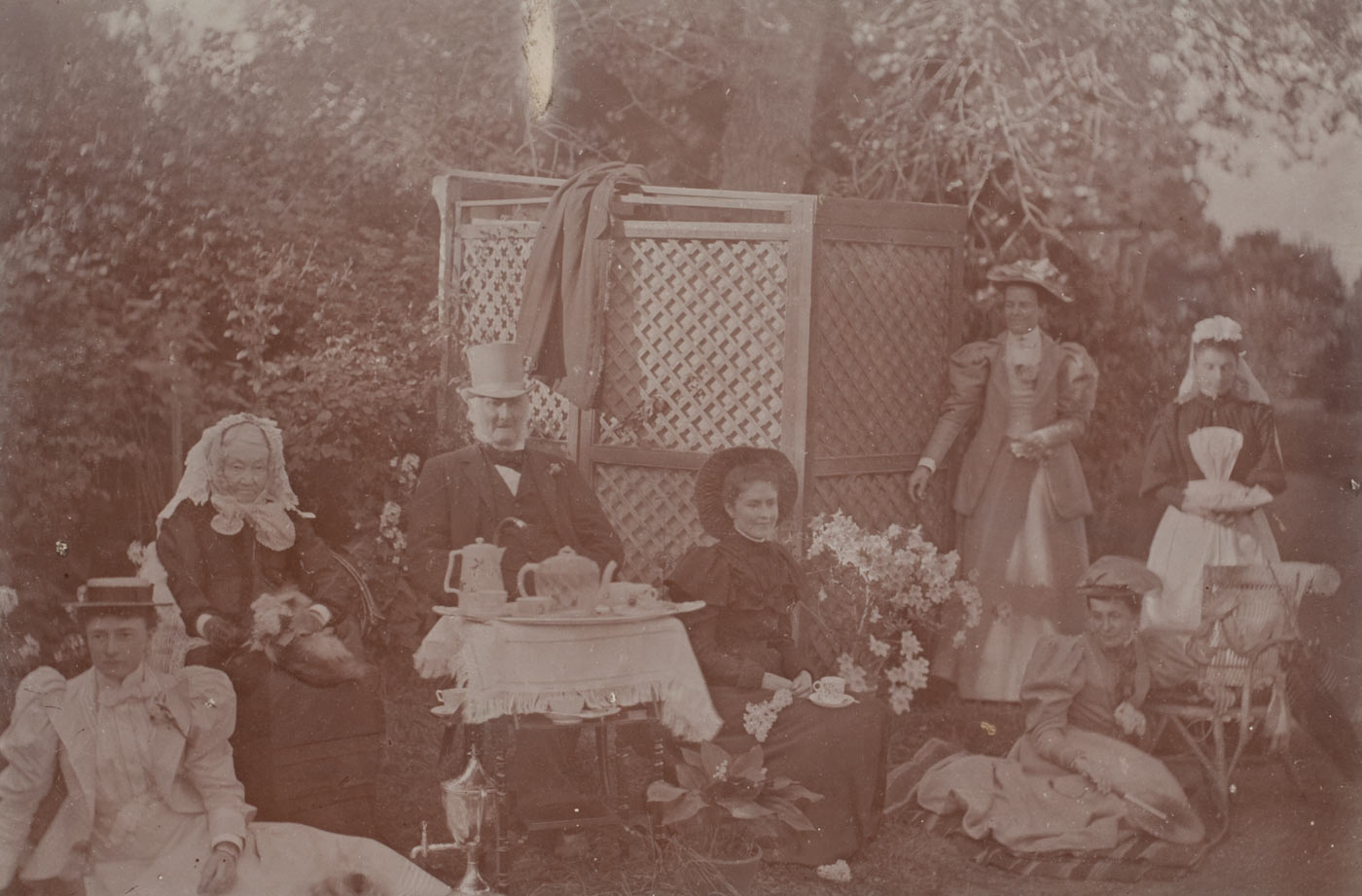 Sepia photograph showing a man and six women taking tea outside in a garden.