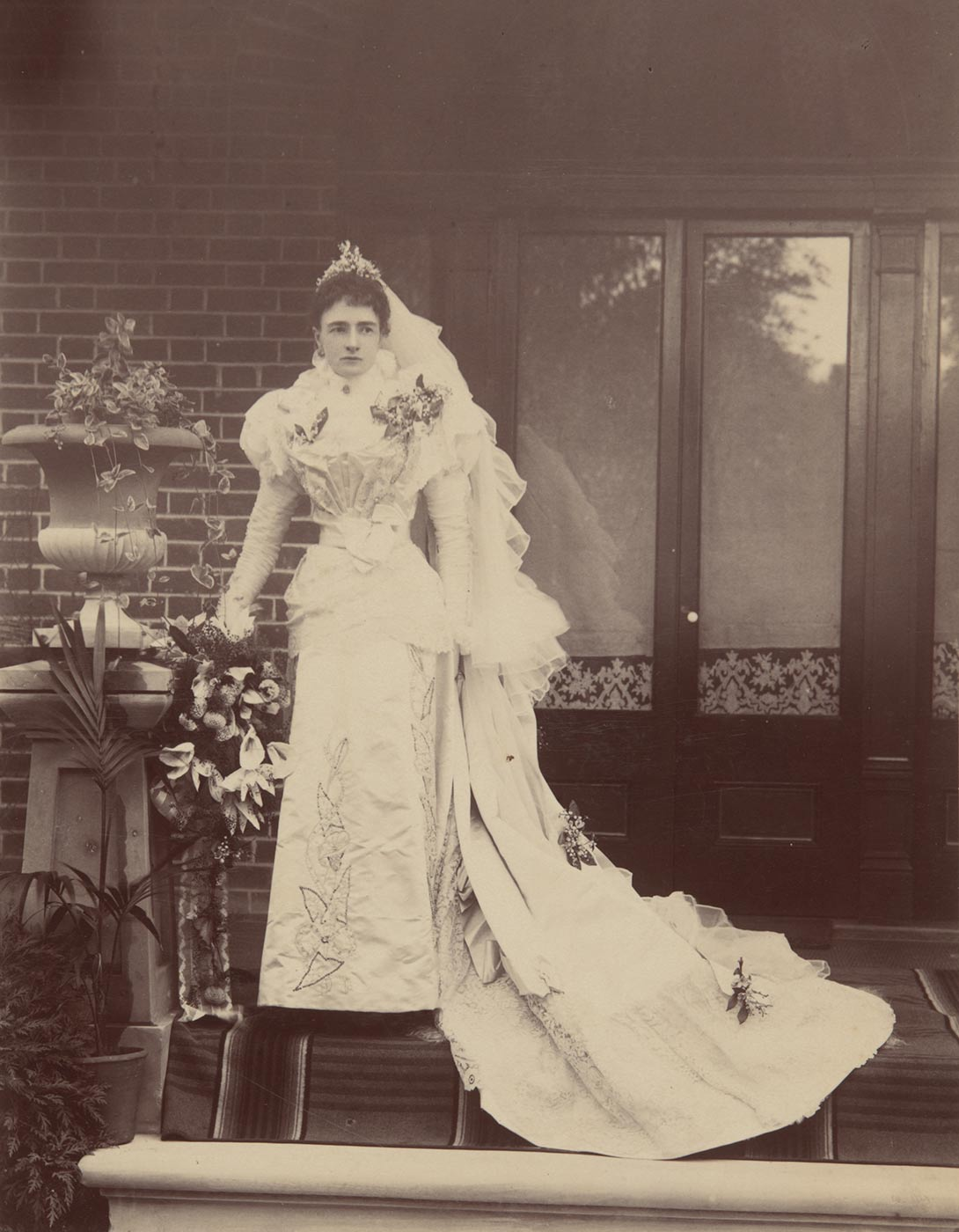 A woman wearing a wedding dress and standing on the front porch of a house. - click to view larger image