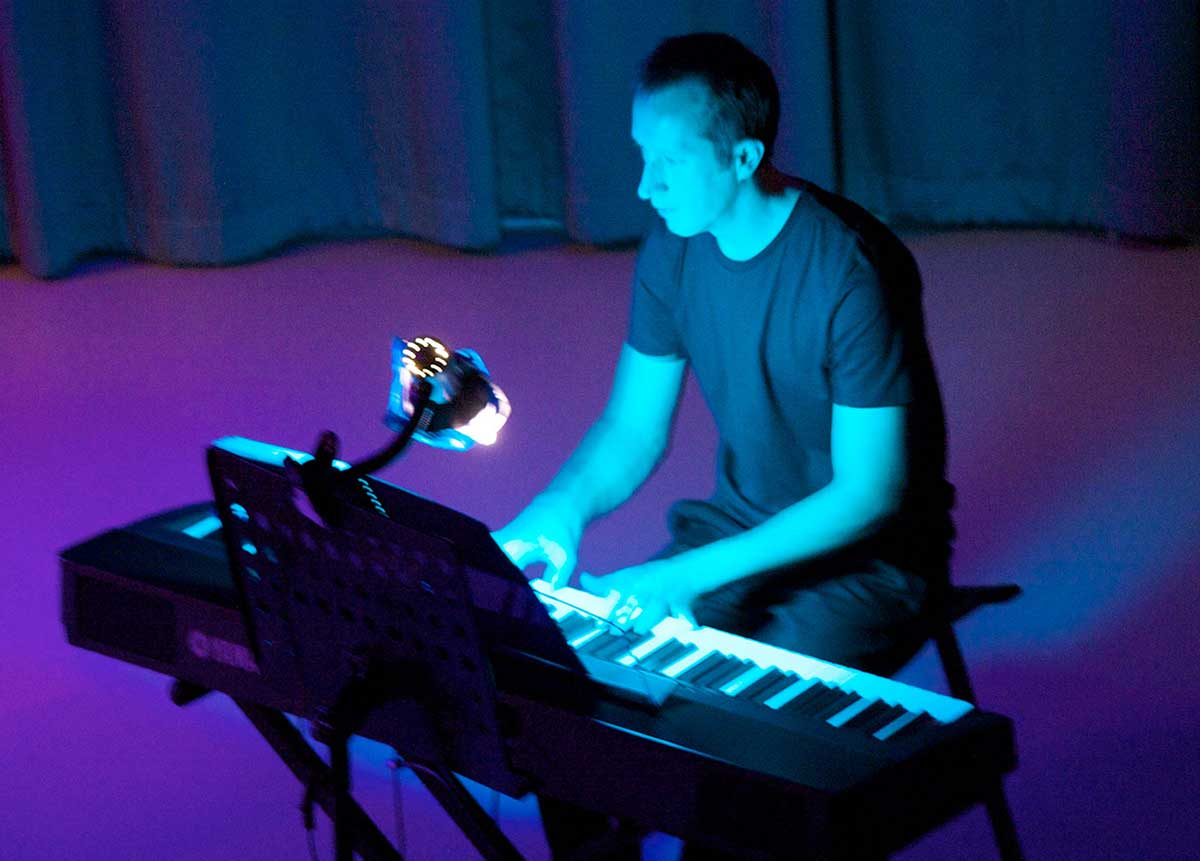 A man playing an electric piano on a stage. - click to view larger image