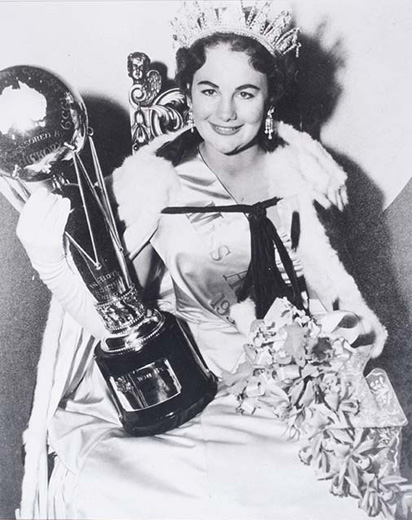 Miss Australia 1959, Joan Stanbury holding the Miss Australia trophy and a bouquet of flowers, wearing the crown, robe and long white gloves - click to view larger image