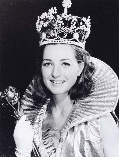 Miss Australia 1969, Suzanne McClelland holding the sceptre wearing the crown a long, gold, frill-collared, sleeveless cape and white gloves - click to view larger image