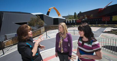 A museum visitor host explains the Garden of Australian Dreams to two visitors. Behind them them is an open area with markings on the ground - a miniature asphalt roadway is painted on the ground and runs diagonally across the image. The Museum's building in the background with the orange loop visible above the roofline.